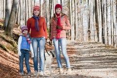 Famille marchant avec le crabot Photographie stock libre de droits