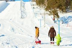 Famille marchant dans la station de sports d'hiver photo stock