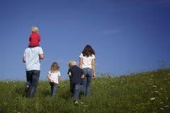 Famille marchant dans le pré, vue par derrière. Photos libres de droits