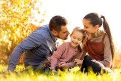 Famille marchant en parc d'automne au coucher du soleil photographie stock libre de droits