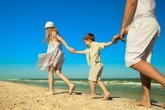 Famille marchant le long de la plage Photo stock