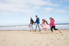 Famille marchant le long de la plage de l'hiver Photographie stock libre de droits