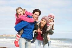 Famille marchant le long de la plage de l'hiver Images stock