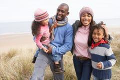 Famille marchant le long des dunes sur la plage de l'hiver Photographie stock libre de droits