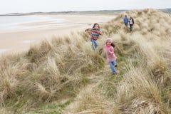 Famille marchant le long des dunes sur la plage de l'hiver Photo stock