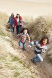 Famille marchant le long des dunes sur la plage de l'hiver image libre de droits
