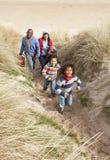 Famille marchant le long des dunes sur la plage de l'hiver image stock