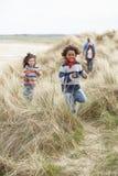 Famille marchant le long des dunes sur la plage de l'hiver photos libres de droits