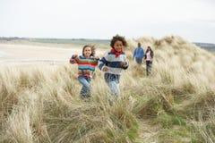 Famille marchant le long des dunes sur la plage de l'hiver Images stock