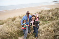 Famille marchant le long des dunes sur la plage de l'hiver Photo libre de droits