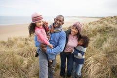 Famille marchant le long des dunes sur la plage de l'hiver Images libres de droits