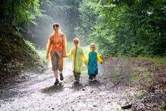 Famille marchant sous la pluie images stock