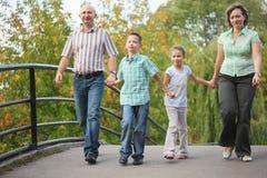 Famille marchant sur la passerelle en stationnement tôt d'automne Image libre de droits