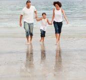 Famille marchant sur une plage images stock