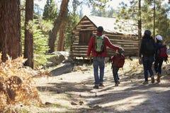 Famille marchant vers une carlingue de rondin dans une forêt, vue arrière image stock