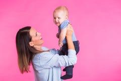 Famille, maternité, parenting, les gens et concept de garde d'enfants - la mère heureuse tient le bébé adorable au-dessus du fond photographie stock libre de droits
