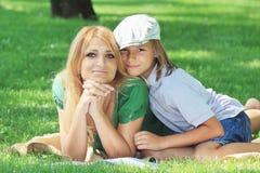 Famille mignonne amicale sur une pelouse d'herbe verte Photographie stock