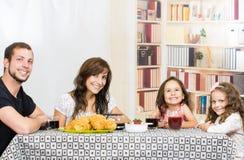 Famille mignonne avec deux filles mangeant le petit déjeuner Images libres de droits