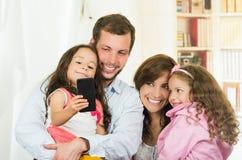 Famille mignonne avec deux petites filles prenant un selfie Photo libre de droits