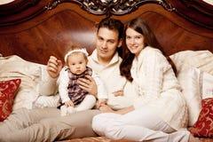 Famille mignonne dans la chambre à coucher Mère, père et fille dans l'I photo stock