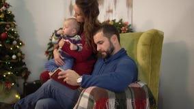 Famille mignonne heureuse passer le temps lisant ensemble le livre Père s'asseyant dans le fauteuil, tenant peu de fils de bébé s banque de vidéos