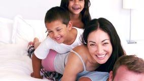 Famille mignonne jouant sur le lit de parents banque de vidéos