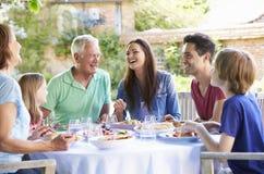Famille multi de génération appréciant le repas extérieur ensemble image stock