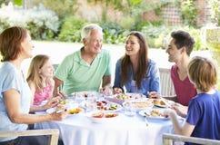 Famille multi de génération appréciant le repas extérieur ensemble photographie stock libre de droits