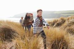 Famille multi de génération en dunes de sable sur la plage d'hiver photographie stock