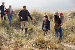 Famille multi de génération en dunes de sable sur la plage d'hiver image libre de droits