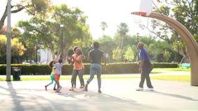 Famille multi de génération jouant le basket-ball dans le mouvement lent banque de vidéos