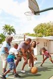 Famille multi de génération jouant le basket-ball ensemble Images stock