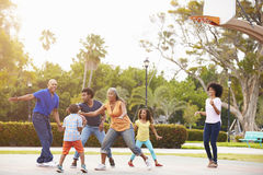 Famille multi de génération jouant le basket-ball ensemble Image stock