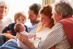 Famille multi de génération se reposant sur Sofa With Newborn Baby Photos stock