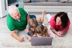 Famille multi de génération utilisant l'ordinateur portable à la maison Photos libres de droits