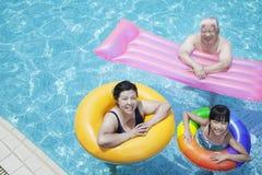 famille Multi-de generations jouant dans la piscine avec les tubes gonflables, regardant l'appareil-photo Photographie stock