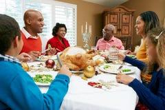 Famille multi de rétablissement ayant le repas de Noël Photos stock