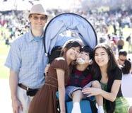 Famille multiraciale dans la foule avec l'enfant handicapé dans le fauteuil roulant Photographie stock