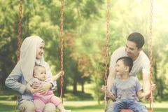 Famille musulmane gaie jouant sur l'oscillation Photos stock