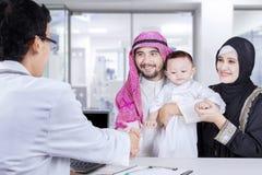 Famille musulmane serrant la main à un pédiatre Photographie stock libre de droits