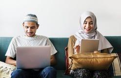 Famille musulmane utilisant les dispositifs numériques à la maison photo stock