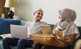 Famille musulmane utilisant les dispositifs numériques à la maison photos stock