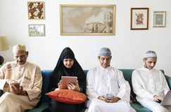 Famille musulmane utilisant les dispositifs numériques à la maison image libre de droits