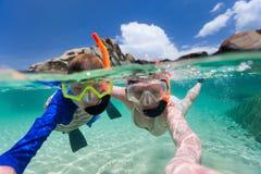 Famille naviguant au schnorchel dans l'eau tropicale Images libres de droits