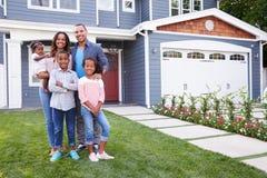 Famille noire heureuse debout en dehors de leur maison image stock