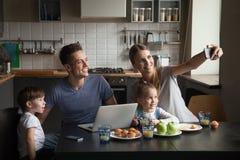 Famille nombreuse heureuse au petit déjeuner prenant le selfie au téléphone images libres de droits