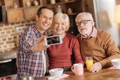 Famille optimiste prenant des selfies tout en prenant le petit déjeuner Photos libres de droits