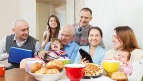 Famille ou groupe heureuse d'amis avec des appareils électroniques Photo stock