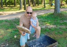 Famille - père et petite fille - avoir une partie de barbecue Photographie stock libre de droits