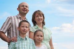 Famille. père, mère, petit garçon et fille sur le ciel Image stock